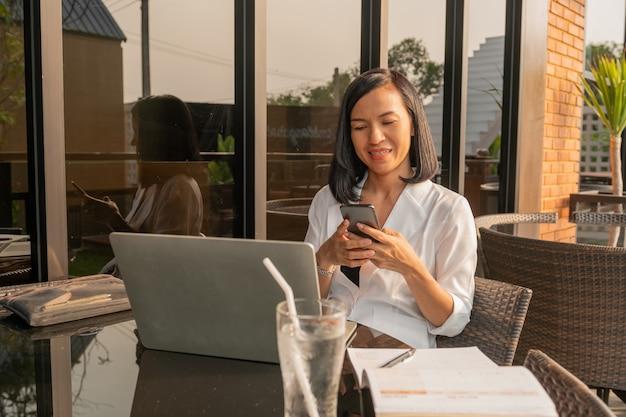 Retrato de mulher de negócios em um café usando um laptop e um telefone celular