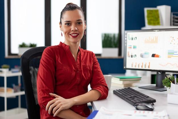 Retrato de mulher de negócios em um escritório corporativo, sentada à mesa