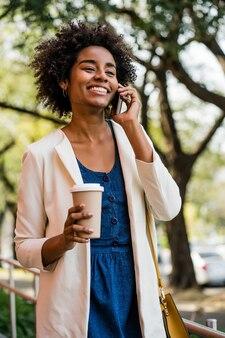 Retrato de mulher de negócios, falando ao telefone e segurando uma xícara de café em pé ao ar livre no parque. conceito de negócios.