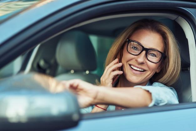 Retrato de mulher de negócios feliz bem-sucedida falando ao telefone celular e sorrindo enquanto dirige um carro