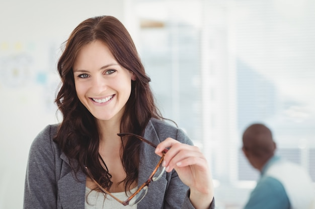 Retrato de mulher de negócios feliz segurando óculos
