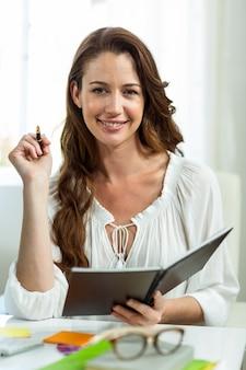 Retrato de mulher de negócios feliz sorrindo enquanto segura o bloco de notas na mesa