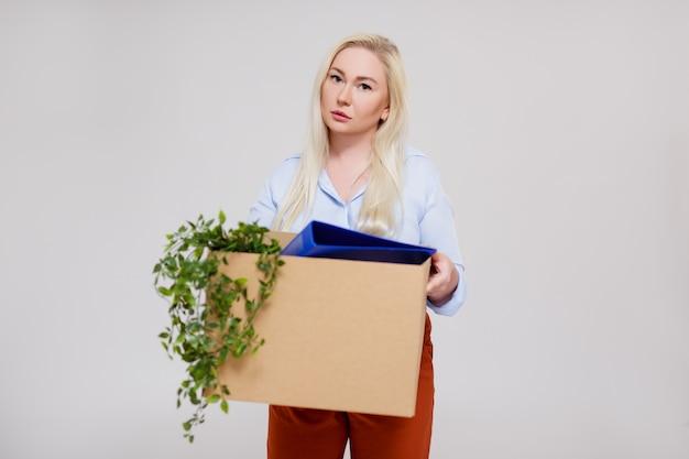 Retrato de mulher de negócios infeliz segurando uma caixa de papelão após ser demitida do emprego, copie o espaço sobre um fundo cinza