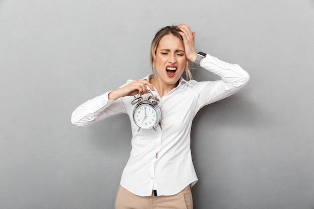 Retrato de mulher de negócios irritada gritando e segurando o despertador no escritório, isolado