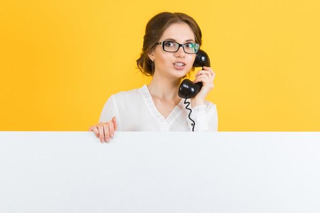 Retrato de mulher de negócios jovem animado bonito confiante com telefone mostrando outdoor em branco sobre fundo amarelo