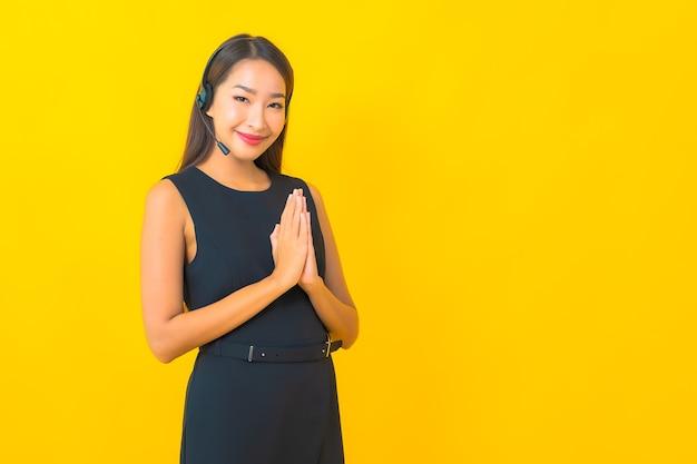 Retrato de mulher de negócios jovem asiática linda com fone de ouvido call center atendimento ao cliente em fundo amarelo