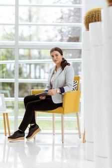 Retrato de mulher de negócios jovem atraente trabalhando on-line com um tablet digital