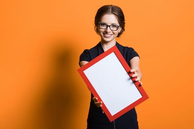Retrato de mulher de negócios jovem bonita confiante segurando o quadro nas mãos de pé na camiseta laranja oferecendo