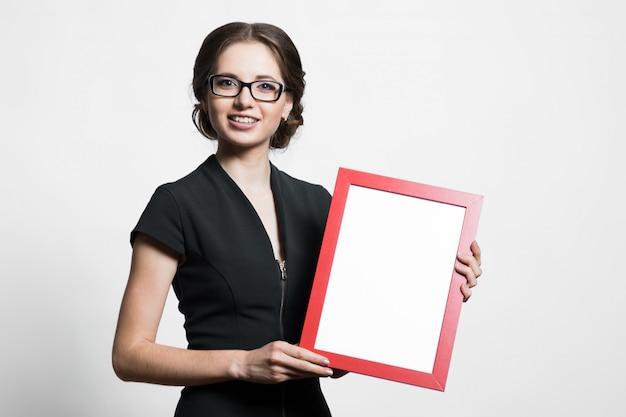 Retrato de mulher de negócios jovem bonita confiante segurando o quadro