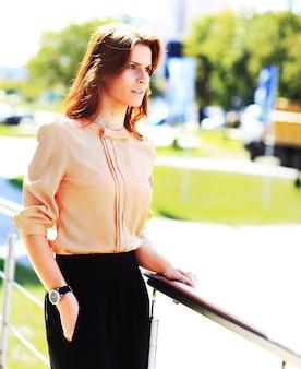 Retrato de mulher de negócios jovem bonito ao ar livre sobre o fundo do edifício
