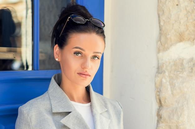 Retrato de mulher de negócios jovem elegante vestindo jaqueta na porta, ao ar livre.