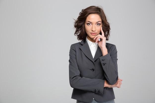 Retrato de mulher de negócios jovem encaracolado bonita confiante com casaco cinza