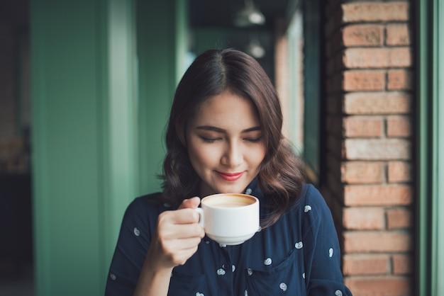 Retrato de mulher de negócios jovem feliz com a caneca nas mãos, bebendo café pela manhã no restaurante