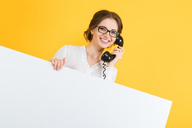 Retrato de mulher de negócios jovem feliz sorridente animado bonito confiante com telefone mostrando o cartaz em branco