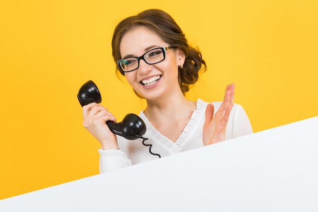 Retrato de mulher de negócios jovem feliz sorridente animado bonito confiante com telefone mostrando outdoor em branco amarelo
