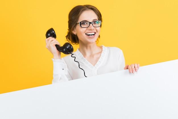 Retrato de mulher de negócios jovem feliz sorridente animado bonito confiante com telefone mostrando outdoor em branco sobre fundo amarelo
