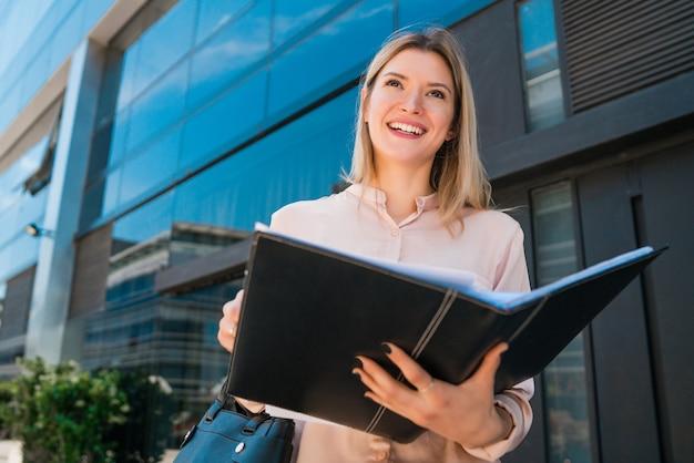 Retrato de mulher de negócios jovem segurando a área de transferência em pé ao ar livre na rua. conceito de negócios.