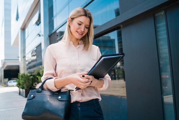 Retrato de mulher de negócios jovem segurando a prancheta em pé ao ar livre na rua. conceito de negócios.