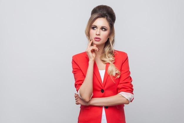 Retrato de mulher de negócios linda confusa com penteado e maquiagem em blazer vermelho chique, em pé, tocando seu rosto e pensando. tiro de estúdio interno, isolado em fundo cinza.