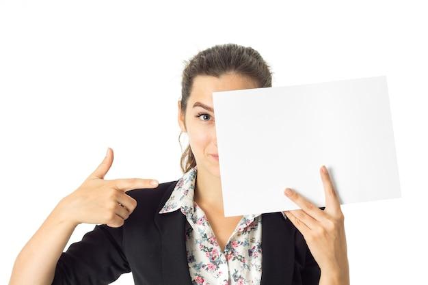 Retrato de mulher de negócios morena atraente de uniforme com um cartaz branco nas mãos, isolado na parede branca