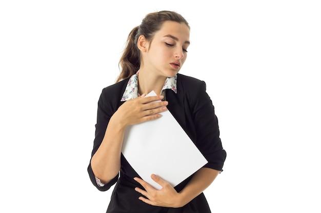 Retrato de mulher de negócios morena bonita de uniforme com um cartaz branco nas mãos, isolado na parede branca