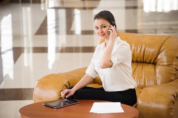 Retrato de mulher de negócios ocupada trabalhando no ipad enquanto está sentado no sofá. pequenos negócios.