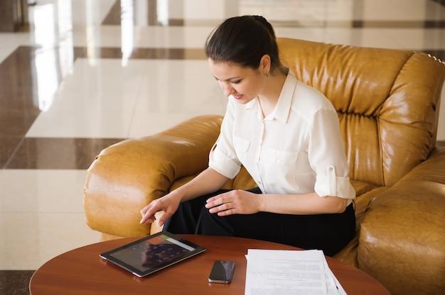 Retrato de mulher de negócios ocupada trabalhando no ipad enquanto está sentado