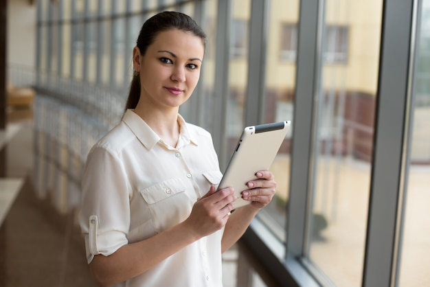 Retrato de mulher de negócios ocupada trabalhando no tablet em pé pela janela no escritório