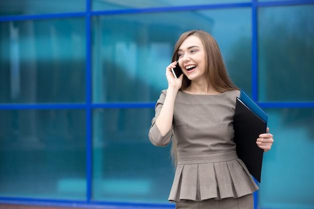 Retrato de mulher de negócios rindo enquanto fala em celular. copie espaço