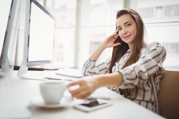 Retrato de mulher de negócios segurando a xícara de café em offic criativo