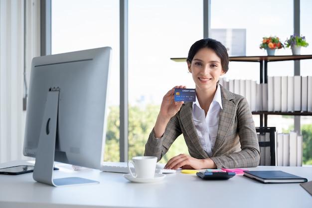 Retrato de mulher de negócios, segurando o cartão de crédito no escritório moderno