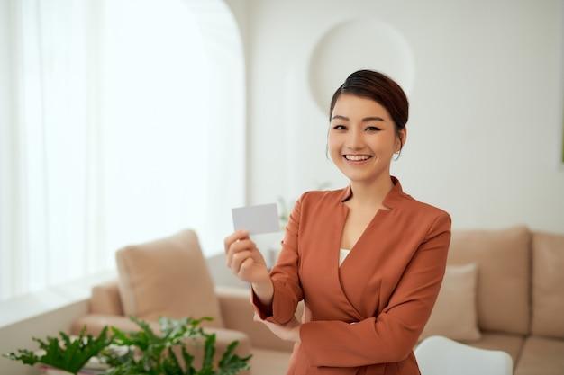 Retrato de mulher de negócios segurando um cartão de visita enquanto está na sala de escritório