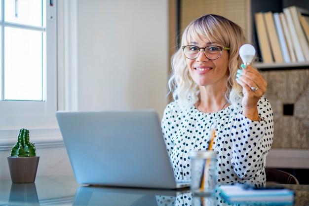 Retrato de mulher de negócios segurando uma lâmpada led enquanto trabalha no laptop na mesa em casa