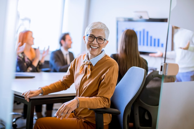 Retrato de mulher de negócios sênior alegre no escritório