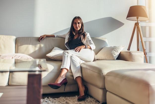 Retrato de mulher de negócios sentada no sofá relaxando depois do trabalho em casa.