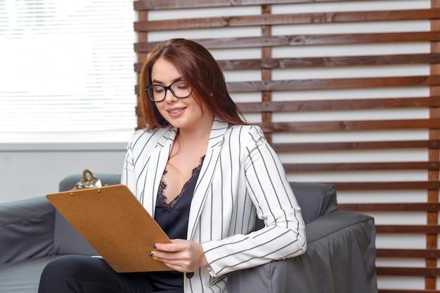 Retrato de mulher de negócios sentado no sofá no escritório moderno