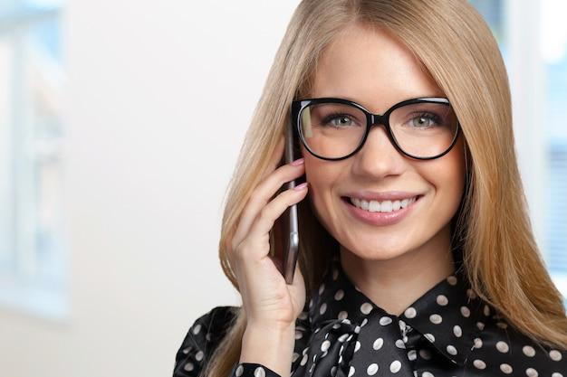 Retrato de mulher de negócios sorridente, falando ao telefone