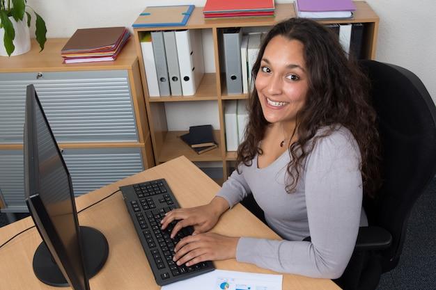 Retrato de mulher de negócios sorridente na mesa com o laptop