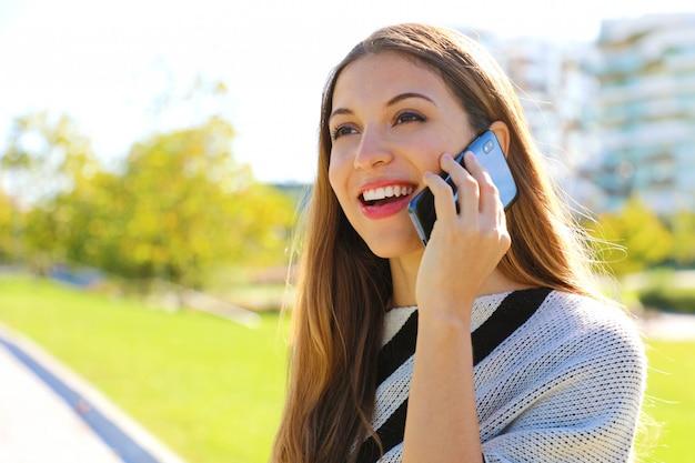 Retrato de mulher de negócios sorridente, tendo uma conversa em seu telefone celular ao ar livre.