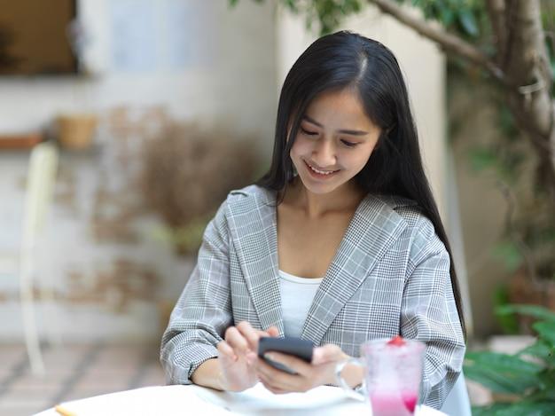 Retrato de mulher de negócios sorrindo e relaxando com o smartphone enquanto está sentada no jardim em casa