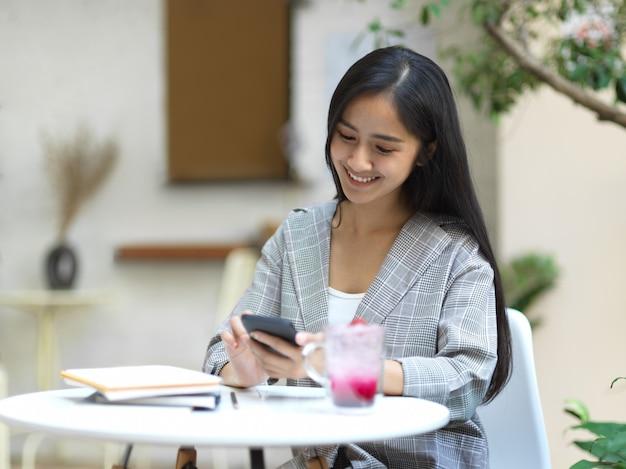 Retrato de mulher de negócios sorrindo e relaxando com smartphone no jardim em casa