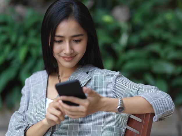 Retrato de mulher de negócios sorrindo e usando smartphone enquanto relaxa no jardim em casa