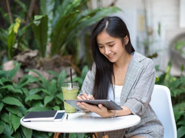 Retrato de mulher de negócios trabalhando com tablet digital na mesa de centro no jardim em casa