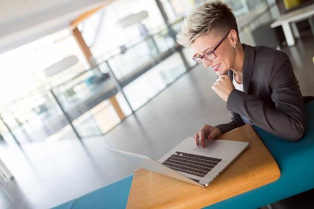 Retrato de mulher de negócios trabalhando no computador em um escritório moderno