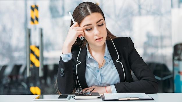 Retrato de mulher de negócios. viciado em trabalho. executivo corporativo sobrecarregado mal sentado no local de trabalho.