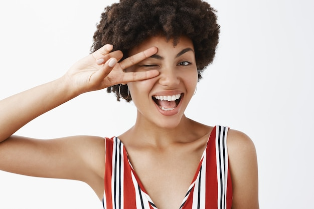 Retrato de mulher de pele escura, feliz e feminina satisfeita se sentindo divertida e animada, cumprimentando melhores amigas, piscando e sorrindo amplamente, mostrando o sinal da vitória sobre os olhos