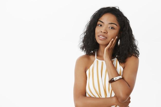 Retrato de mulher de pele escura, feminina e sensual, tocando o rosto suavemente