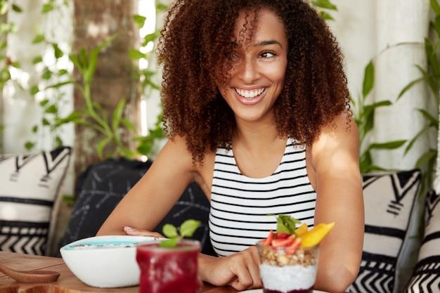 Retrato de mulher de pele morena positiva tem expressão positiva, parece feliz de lado porque tem expressão sonhadora e pensa em algo bom, come sobremesa exótica saborosa, tem um largo sorriso no rosto