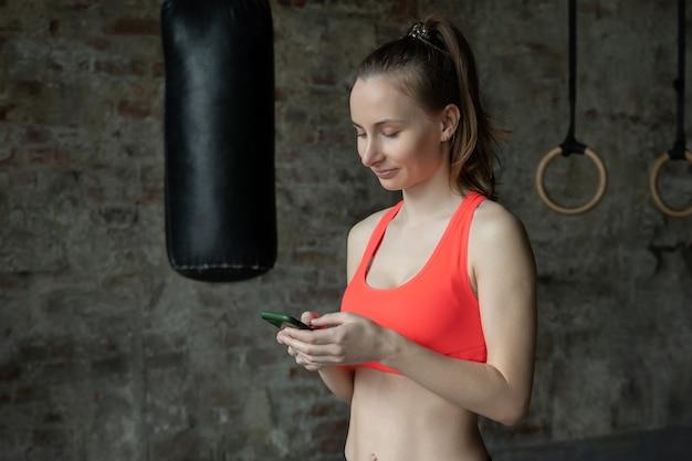 Retrato de mulher de personal trainer usando smartphone no ginásio de fitness