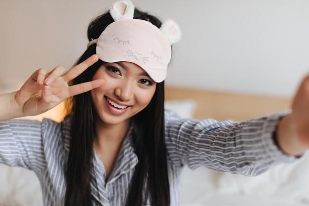 Retrato de mulher de pijama listrado, mostrando sinal de paz